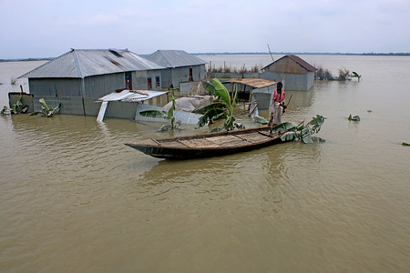 A Bangladeshi man pulls a small boat in front of his house through flood waters following heavy mosoon rains in Tangail. Over million people have been affected by floods triggered by the monsoon rains and overflowing river in north, north-eastern and hilly regions in Bangladesh.