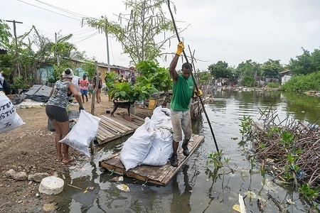 People collect plastic waste from a river at the La Boquilla during a clean-up session in Cartagena. Fundacion CoraJeM works in educating and creating opportunities for the people in need. Teaching them culture and values, it allows them to build up a better future and live with more dignity.