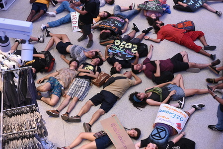 Activists lay on the ground pretending to be dead in a performance during the protest. Extinction Rebellion activists gathered at Gran Via Primark store in Madrid to protest against textile industries, and to demand to the Spanish government act against climate change.