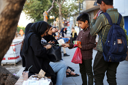 Shir Agha, a child labourer sells gum to a young woman on the streets. Child labour is a serious issue in Iran, estimated to be between 3 to 7 million, with 60,000 children joining every year.