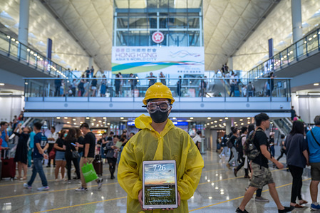 A protester wears a yellow raincoat and a yellow helmet during the protest at the Hong Kong international airport arrival hall. Thousands of anti government protesters staged a sit in protest at the Hong Kong international airport terminal, the first of three straight days of demonstrations after clashes last week triggered fears that a wider confrontation could erupt in the city.