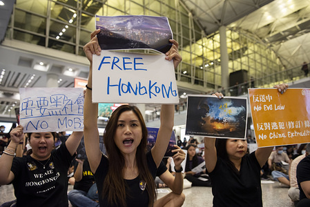 Protesters hold placards during the sit in protest at the airport arrival hall. Hundreds of anti government protesters staged a sit in protest at the Hong Kong international airport terminal, the first of three straight days of demonstrations after clashes last week triggered fears that a wider confrontation could erupt in the city