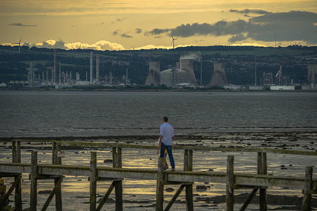 Father and child walk on pier with INEOS Grangemouth Oil and Gas Refinery in background.