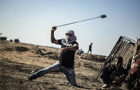 A Palestinian protester uses a slingshot to hurl stones during the clashes. Palestinians clashes with Israeli security forces demanding for an end to the Israeli blockade of Gaza and the right of return to their homes at the border fence between Israel and Gaza in the southern Gaza Strip.