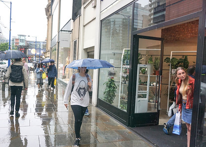 People walk through the city center of Manchester with umbrellas during heavy rain.