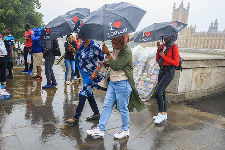 Tourists on Westminster Bridge  with souvenir umbrellas during rain showers as a month's rainfall was expected in three hours with the risk of flooding in some areas of  the United Kingdom.