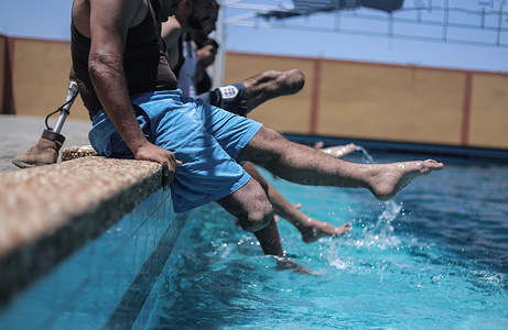 Palestinian amputees, who lost a leg in rounds of violence with Israel, take part in a swimming training session in Gaza City.