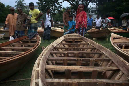 Buyers admire boats at the boat market, in Manukganj's Ghior Upazila Due to the flow of Padma, Jamuna, Dhaleswari, Ichhamati, and Kaliganga through the district, lowlands go under water during monsoon leaving no option for the residents but to buy a boat. Residents of these areas are using boats for decades, according to locals.