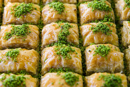 Baklava dessert, a traditional Middle Eastern rich, sweet dessert pastry made of layers of filo filled with chopped nuts, sweetened and held together with syrup or honey seen for sale inside a bakery at a Turkish restaurant in London.