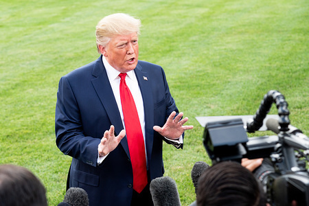 President Donald Trump speaking with the press next to the South Lawn at the White House in Washington, DC.
