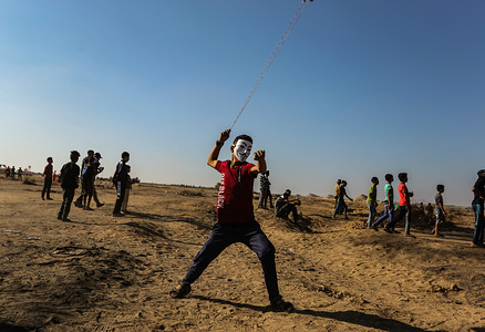 A Palestinian demonstrator seen throwing stones using a slingshot during the clashes. At least 51 Palestinians were injured on Friday afternoon in the weekly anti-Israel protest in the eastern Gaza Strip close to the border with Israel.