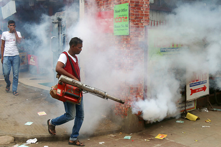 A Dhaka City Corporation worker fumigates the area to kill mosquitoes during a Campaign in Dhaka.