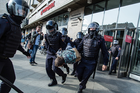 Police officers detain a man during an unsanctioned rally in the centre of Moscow, Russia. Moscow police detained more than 300 people who were protesting against the exclusion of some independent and opposition candidates from the city council ballot, a monitoring group said.