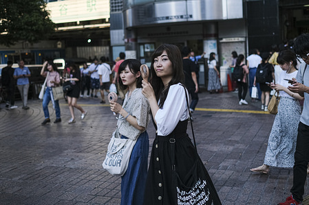 Women hold small portable fans at the Shibuya crossing in Tokyo. A deadly heat wave that swept across Japan has killed at least 11 people as temperatures exceed 30 degree Celsius in many parts of country.