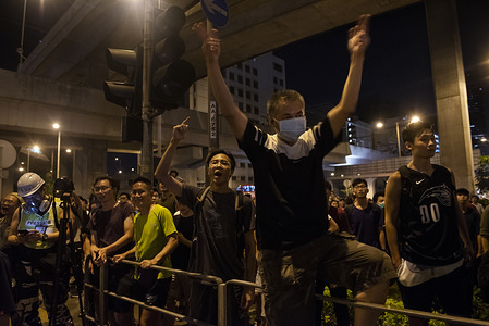 Protesters shout profanities against riot police officers.  Hong Kong protesters ignored police warnings and continued with the latest series of demonstrations targeting Hong Kong government and numerous police stations.