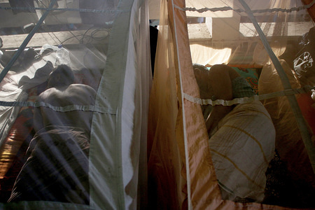 People sleep under the mosquito net to protect themselves from a recent dengue outbreak in Dhaka. The dengue situation in the country is getting worse this year.