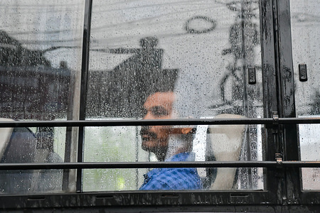A man looks through the half blurred window pane of a bus with rain drops during a rainy day in kolkata. Gangetic West Bengal, the major part of Kolkata at present is the most rain deficient region of the country with a deficiency of 47%.
