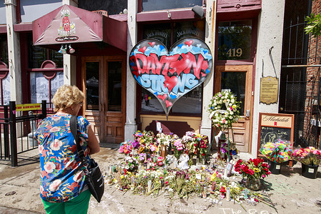 A woman stops to look at a memorial on 5th Street at the site of Sunday morning's mass shooting that left 9 dead, and 27 wounded, Wednesday, August 7, 2019 in Dayton, Ohio. Trump visited a nearby hospital but did not visit the site of the shooting before flying to El Paso, Texas, which was also the site of a mass shooting.