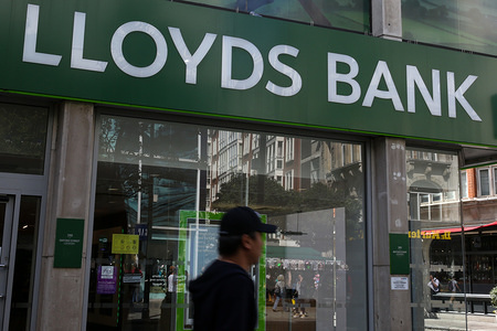 A man walks past a branch of Lloyds Bank in central London.