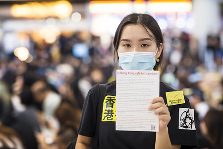 """A female protester holding a leaflet with information about the ongoing protests in Hong Kong during the demonstration at the airport. Thousands of protesters took to the arrival hall of the Hong Kong international airport under the name """"Greetings from HKers Assembly"""" to catch the attention by the international travelers who just landed in Hong Kong about the current unrest situation in the city."""
