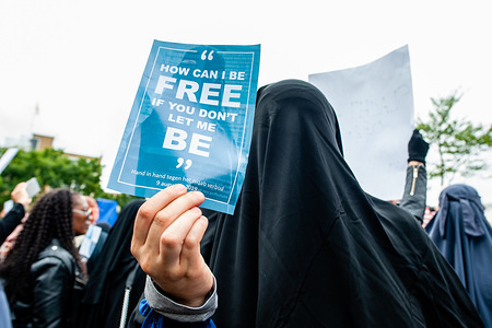 A woman wearing a niqab holds a placard that says How can I be free, if you don't let me be during the protest. Hundreds of people gathered in The Hague after The Netherlands approves a limited ban on 'face-covering clothing', this law includes also niqabs and burqas. The demonstration was in silence to show their solidarity with women wearing niqabs. The Netherlands is the sixth EU country to prohibit face-covering clothing in public buildings.