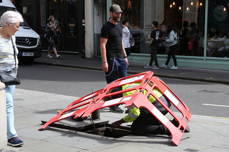 A workman carries out maintenance on a windy day in London. Strong winds are causing disruption, with severe weather warnings in places across the UK.