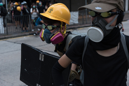 A protester shields himself with school binder during a demonstration against the government. Hundreds of antigovernment protesters continued to take to the streets demanding the withdrawal of the extradition bill, now just one among four other major requests. Protesters continued their method of building barriers while police barraged them with tear gas. A police charge eventually ended the arrests of several protesters.