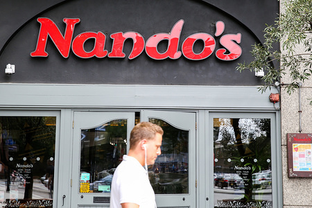 A man is seem walking past a branch of Nando's in central London.  Nando's is a South African restaurant chain, specialising in peri-peri style chicken dishes.