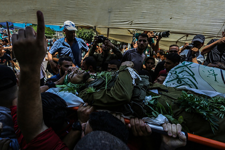 (EDITOR'S NOTE: Image depicts death.) Mourners carry the body of Palestinian militant, during the funeral procession. Marwan Nasser, a Palestinian fighter was fired at by Israeli soldiers at the Gaza border. Palestinian medics said the fighter was killed at the northern Gaza Strip. It was the second such incident since 10 August, when Israeli troops shot dead four Palestinians fighters who attempted to cross the volatile border in the eastern Gaza Strip.