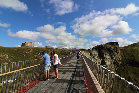 People on the controversial new footbridge re-connecting both halves of Tintagel Castle for the first time in 500 years, has at long last been opened.  The medieval castle on the Cornwall coast - long rumoured to be the site of King Arthur's legendary Camelot - lost its original bridge sometime between the 15th and 16th centuries. A storm which hit the Cornish coast delayed the bridge's opening.
