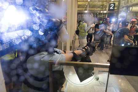 A police officer aims his gun against protesters during the demonstration. Anti-government protesters peacefully sat-in at the Hong Kong International Airport for the 5th consecutive day until later in the evening where various events led to intense confrontation and violence with the police. The sit-in led to mass flight cancellations and aimed to raise international awareness of protesters' fight against the extradition bill and of police brutality at the protest.