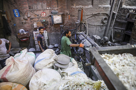 """A man works at the plastic recycling factory in Mokattam. The Garbage City is a district of Cairo where the Christian population called """"Zabbaleen"""" work thanks to the garbage of the entire city of Cairo that is brought here to be sorted, recycled and resold. The livelihood of this population depends exclusively from waste of Egyptian megalopolis."""