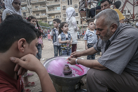 A man prepares candy floss for children on a street which was destroyed by the Russia and the Syrian regime.