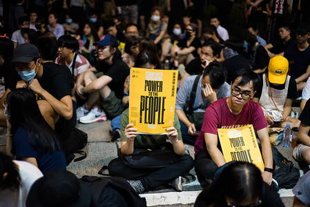 """A protester holds up a """"Power to the People"""" placard during the rally. Demonstrators organized a peaceful rally aimed at building momentum going into the 10th weekend of protests. Rally organizers gave various speeches and displayed videos of various members of British Parliament showing support for Hong Kong's anti-protesters. The demands made by protesters related to the withdrawal of the extradition bill have yet to be resolved by the government."""