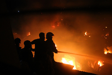 Fire-fighting units with the help of local people are seen trying to douse the fire that broke out at Mirpur slum in Dhaka. A total of 24 units of firefighters brought the blaze under control at around 10:35pm, over three hours after it originated at the slum around 7:20pm on Friday evening and soon engulfed the shanties there, said sources at Fire Service and Civil Defence control room.