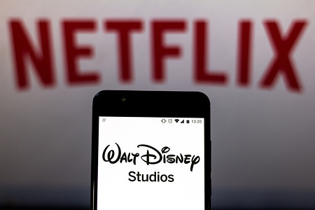 In this photo illustration the Walt Disney Studios logo is seen displayed on a smartphone and logo Netflix on the blurred background.
