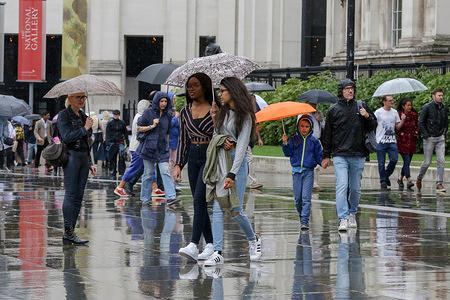 People use umbrellas during rain in London.