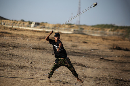 A Palestinian protester hurling stones with a slingshot during clashes between Palestinian demonstrators and Israeli forces across the fence between Gaza and Israel close to Khan Younis in the southern Gaza Strip while demonstrating demanding the lifting of the siege imposed on the citizenship for years.