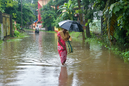 A woman wades while holding an umbrella after the heavy rainfall in Kolkata.