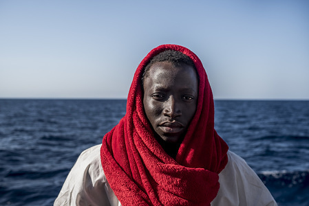 Essah Sanneh is from Gambia, he is 15 years old and started this migrant route  3 and a half years ago. He passed through Senegal, Mali, Burkina, Nigeria and the Sahara heading to Libya. Passing through the Sahara desert was the hardest part as he says, you'll continuously see your fellows dying in the desert and other dead bodies around. The Spanish NGO Proactiva Open Arms rescued 378 migrants. They were 20 miles out from the Libyan coast. Since the beginning of the year, nearly 3.000 people have lost their lives in the Mediterranean Sea. Even if one of every 53 has died crossing, migrants keep on trying to leave Libya because they say that life in Libya is really difficult.