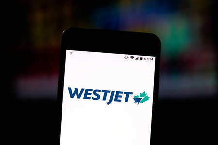 In this photo illustration the WestJet Airlines logo is displayed on a smartphone.