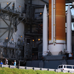People stand close to the twin solid rocket motors at the base of a United Launch Alliance Delta IV rocket which stands at space launch complex 37 at Cape Canaveral Air Force Station in preparation for a scheduled launch at 9 a.m. ET, on August 22, 2019. The rocket will deliver the second GPS III Magellan spacecraft to a medium earth orbit for the U.S. Air Force.