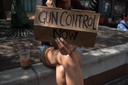 A woman holds a placard that say gun control now during a gun reform rally that was held in Dayton, Ohio in the wake of a mass shooting at the area earlier this month that left 9 dead and 27 wounded.
