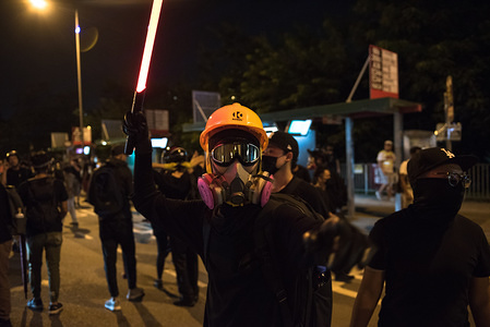 A protester wields a toy lightsaber as he directs other protesters on where to go during the demonstration. Anti-government protesters held a silent assembly in Yuen Long to mark the one-month anniversary of the violent attack that was carried out by white-shirted thugs. Protesters later faced off against riot police before dispersing onto trains. Protesters have yet to see progress on the full withdrawal of the extradition bill and are becoming increasingly frustrated with the police's inability to make key arrests related to the original Yuen Long attack.