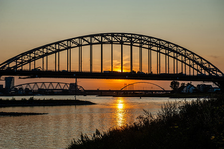 View of the Waalbrug bridge during sunset. The Ooijpolder is a beautiful area for walking and recreation close to the Waalbrug Bridge and surrounded by the Waal River. The area is located east of the city of Nijmegen in the province of Gelderland.