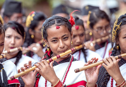 Girls play flutes during the Festival. People celebrate Gai Jatra or cow festival in the memory of departed souls in the past year. It is believed that cows guide the departed souls to cross the river to get to heaven.