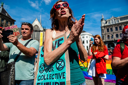 A woman with a placard claps hands during the demonstration. Extinction Rebellion group activists in Amsterdam organized a demonstration in solidarity with rainforest protectors and Amazon activists across the world. Hundreds of people gathered around the Dam square to show their support.