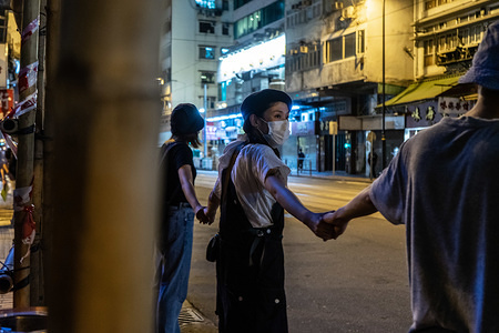 """Hong Kong protesters of different ages hold hands to form human chain across the city to call for democracy. Thousands of Hong Kong protesters link hands to form human chain across the city to call for democracy. The chains, which traced three subway routes, totaled around 40 kilometers (25 miles) in length. The protesters said they were inspired by the """"Baltic Way', when millions created a chain across three countries (Estonia, Latvia and Lithuania) to protest Soviet occupation exactly 30 years ago, and is the latest in the nearly 11-week-old movement that began with calls to scrap a now-suspended extradition bill and has broadened to include demands for full democracy and an independent inquiry into alleged police brutality."""