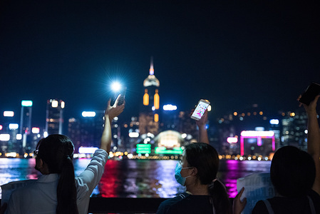 Protesters shine their phone lights while facing the harbour during the demonstration. Protesters held hands to create long human chains in peaceful protest against the extradition bill. Some protesters carried various placards asking and thanking other countries for their support while others also shined their phone lights as a sign of unity and peace.