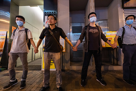 """Protester holding hands to form a human chain during the Hong Kong way event. Thousands of Hong Kong protesters link hands to form human chain across the city to call for democracy during the Hong Kong way event. The chains, which traced three subway routes, totaled around 40 kilometers (25 miles) in length. The protesters said they were inspired by the """"Baltic Way', when millions created a chain across three countries (Estonia, Latvia and Lithuania) to protest Soviet occupation exactly 30 years ago, and is the latest in the nearly 11-week-old movement that began with calls to scrap a now-suspended extradition bill and has broadened to include demands for full democracy and an independent inquiry into alleged police brutality."""